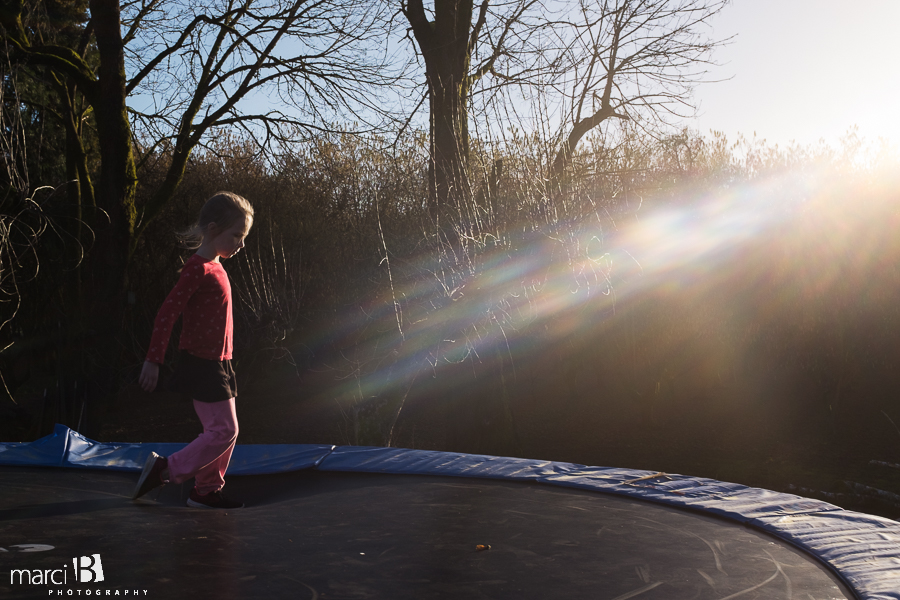 winter on the trampoline - sun in the PNW winter - girl on trampoline
